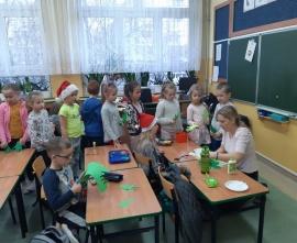 Uczniowie klasy 1b na bożonarodzeniowych warsztatach plastycznych korzystają z pomocy osoby prowadzacej