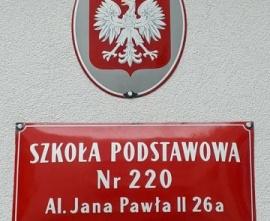 Fragment budynku szkoły z godłem polskim i tablicą