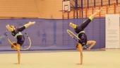 Dwie gimnastyczki ćwiczące z obręczami.